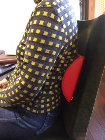 薄目のランバーサポートを腰に当てる女性