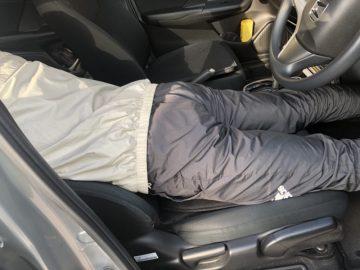 車中で腰を反らして腰痛対策している図