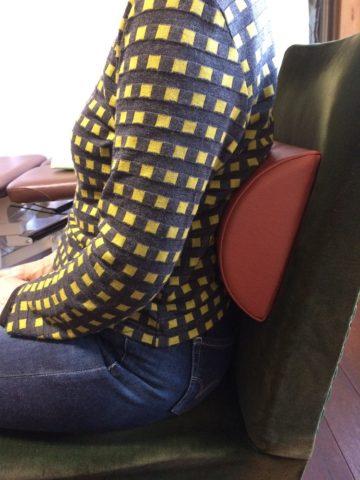 厚目のランバーサポートを腰に入れる女性